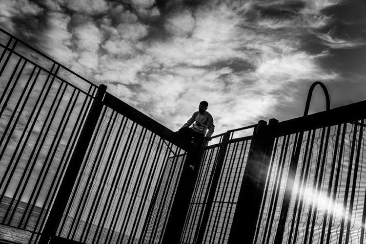 Niño marroquí salta la cerca que rodea al puerto de Melilla.